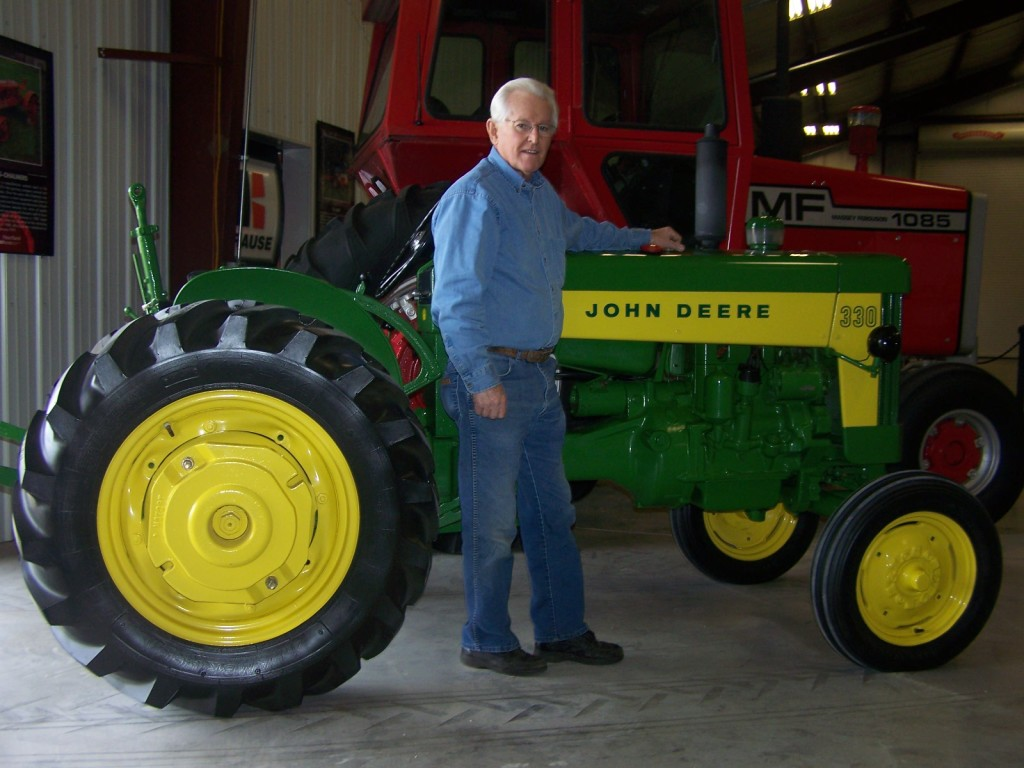 John Cannon by one of his many prized John Deere restored tractors.